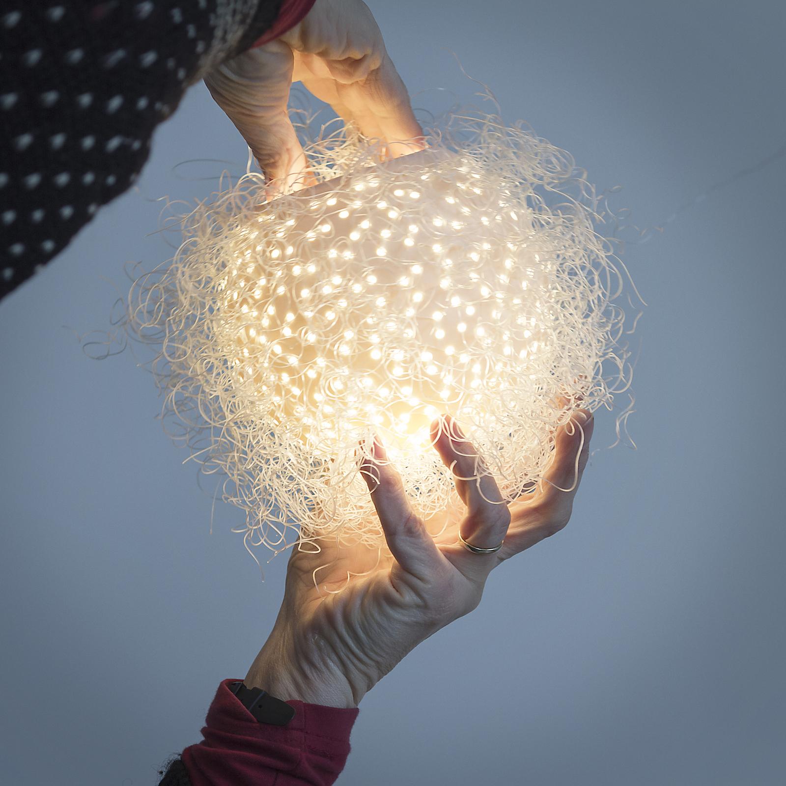 Hands holding porcelain globe pendant