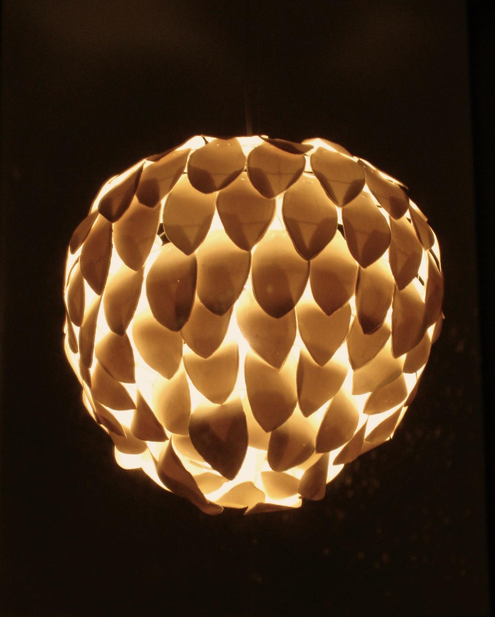 Large chandelier composed of porcelain petals lit in dark room