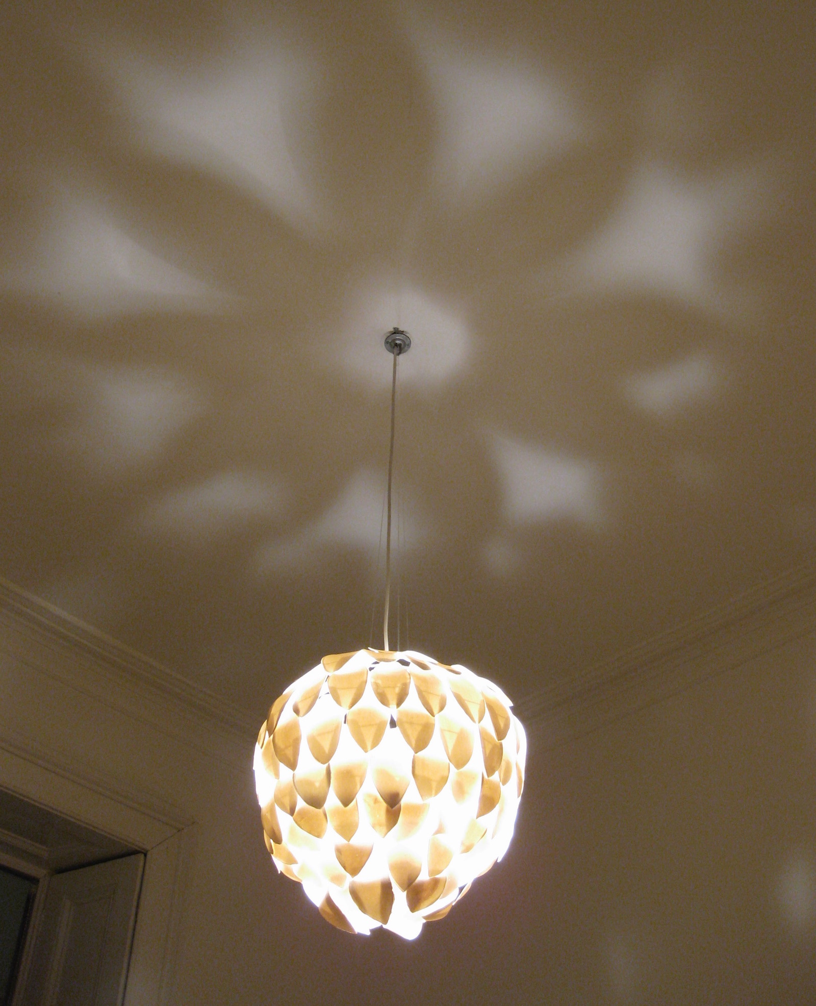 Flower shaped shadows created by chandelier on ceiling