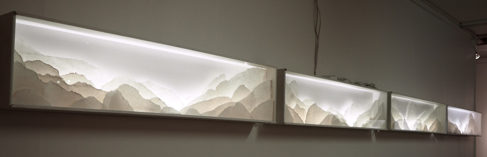 Row of several backlit porcelain landscape dioramas