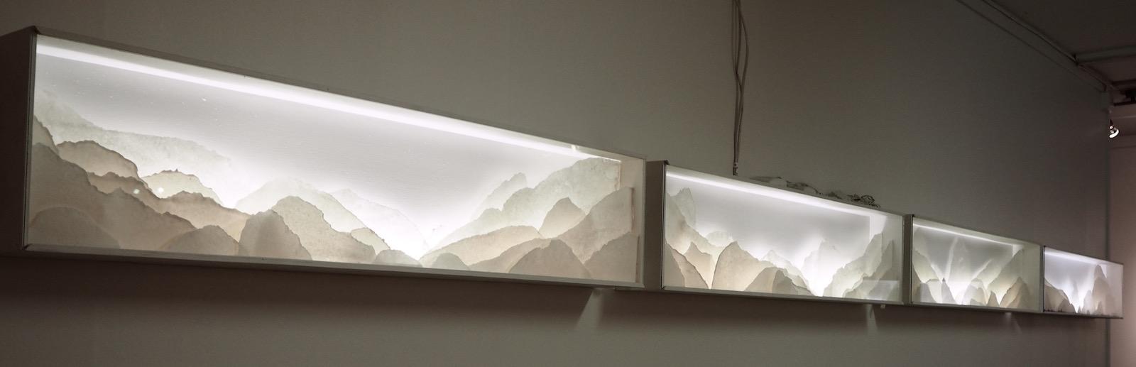 Row of several backlit porcelain landscape dioramas