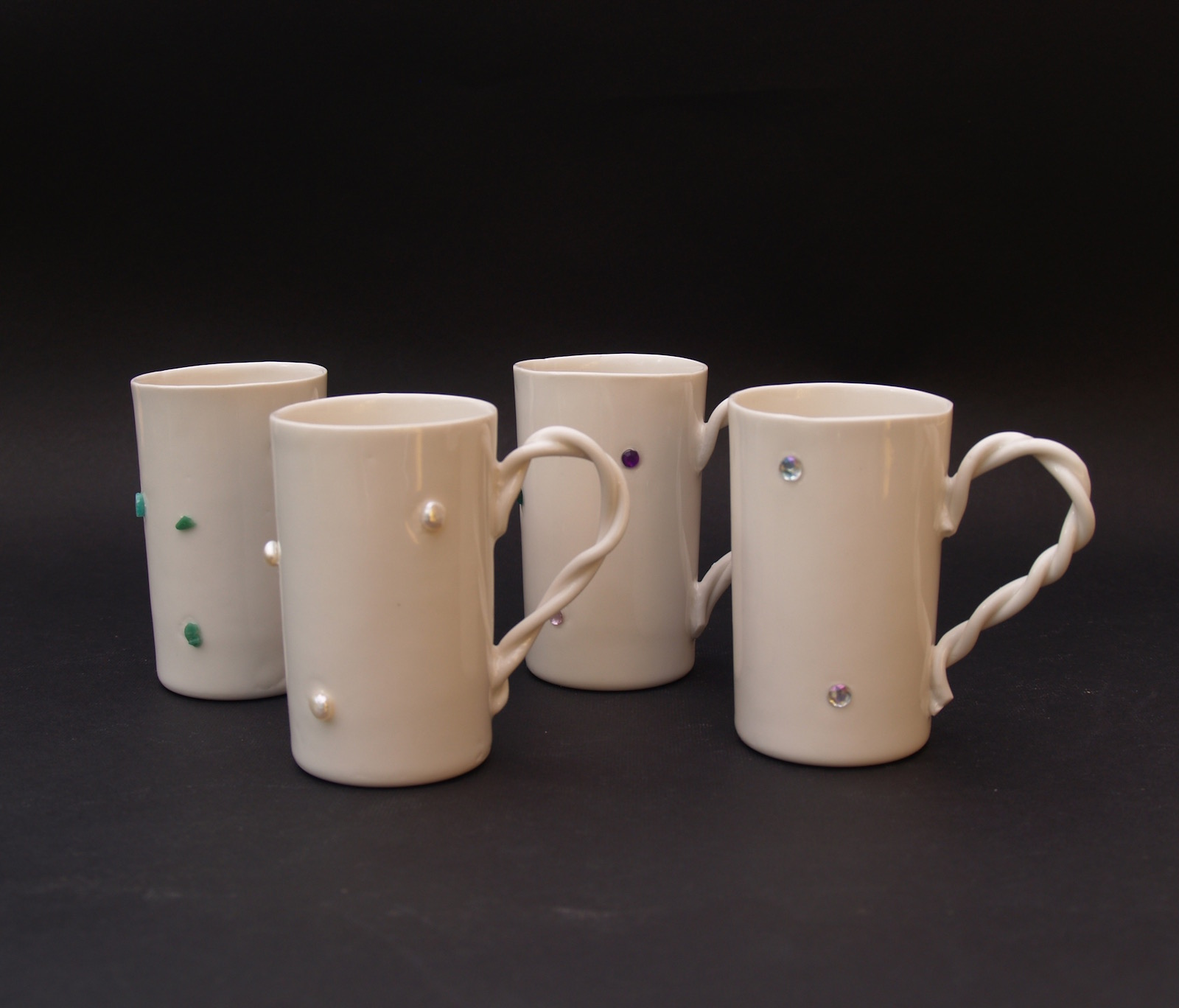 Small bejeweled porcelain mugs with twirled handles
