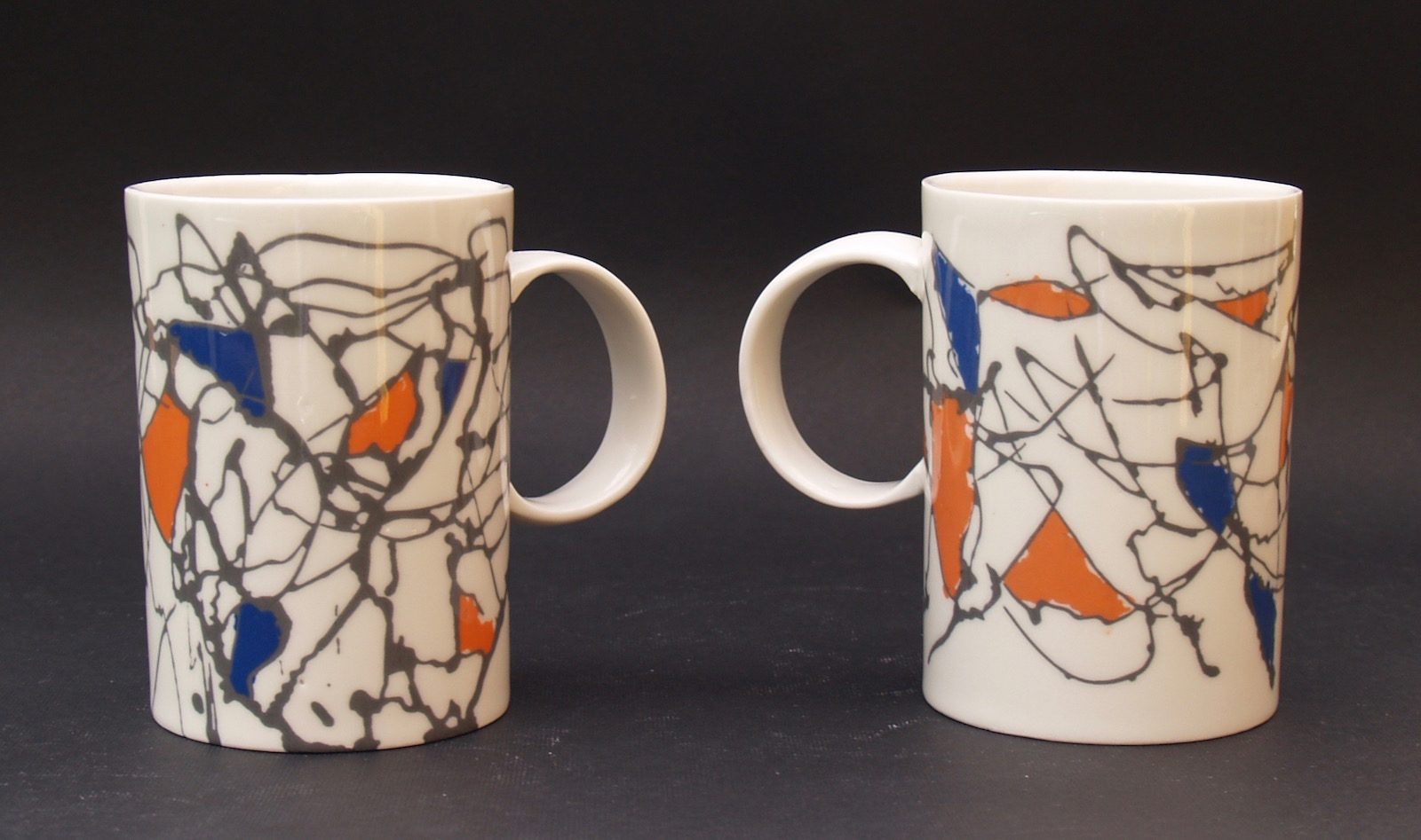 Large porcelain mugs with abstract pattern in black, orange and blue