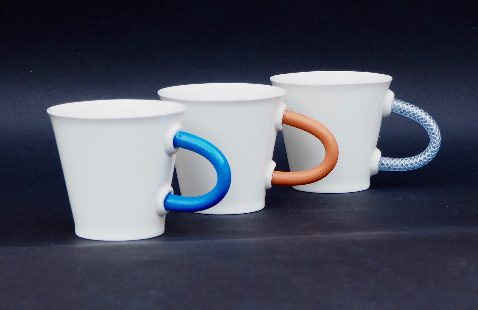 Porcelain mugs with rubber handles in various colours