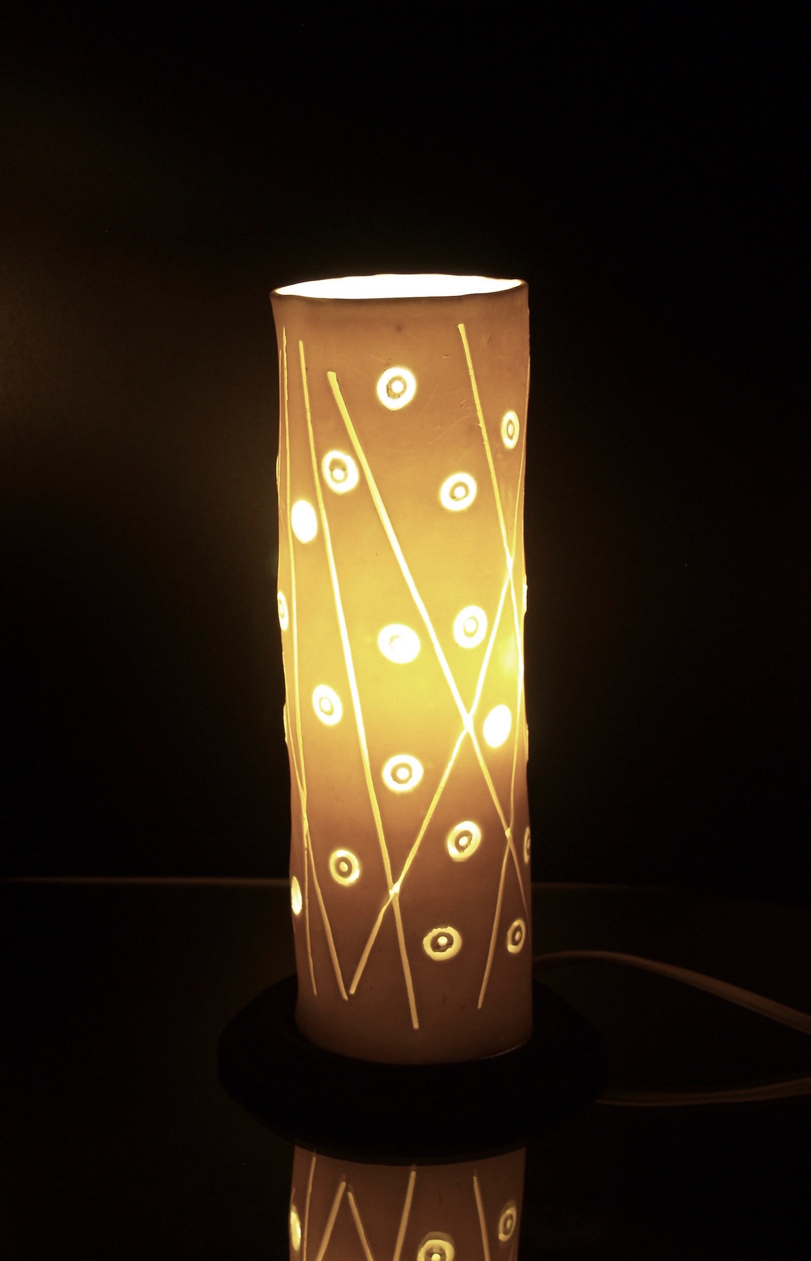 Cylinder shaped table lamp with abstract pattern of dots and lines