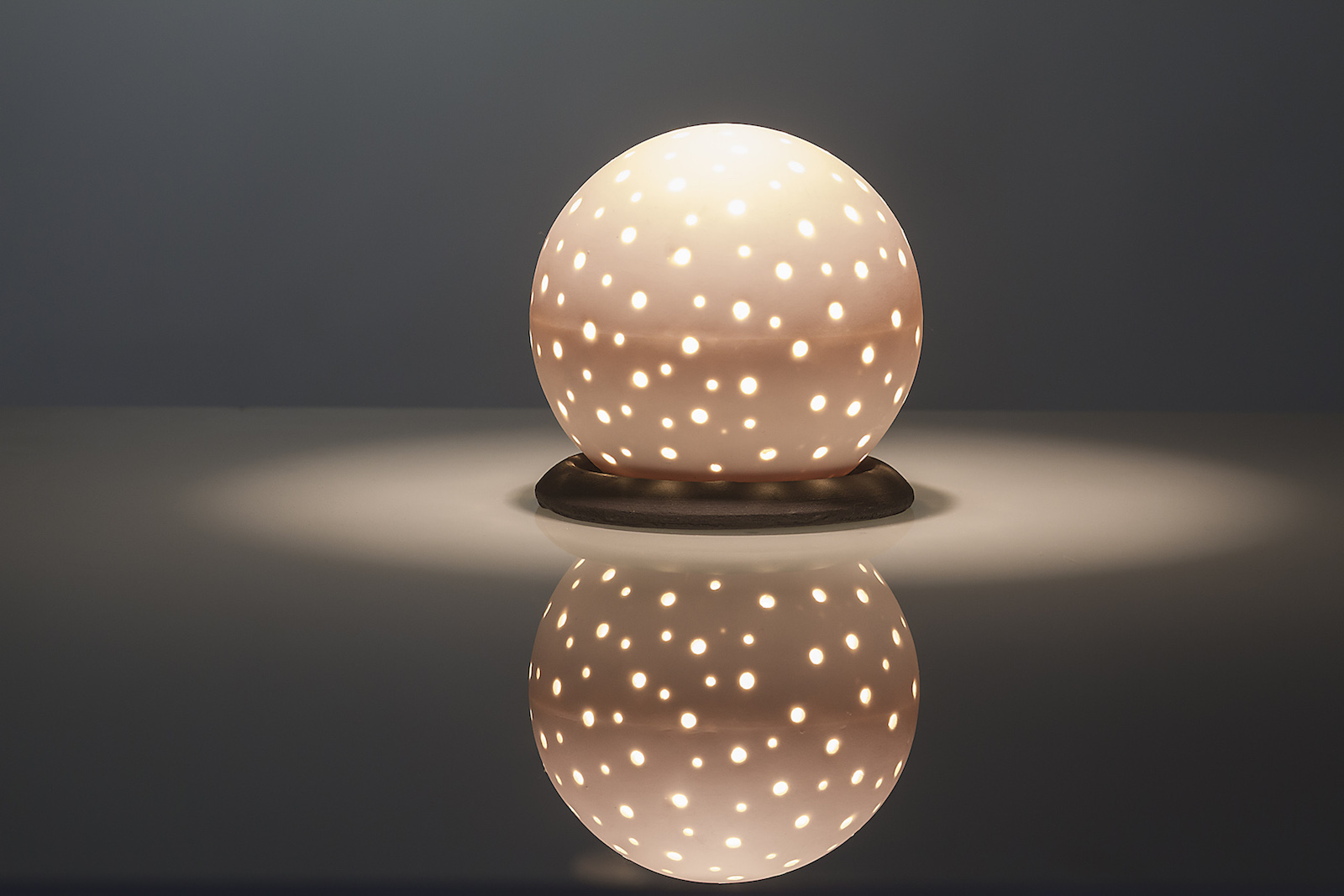 Perforated porcelain globe shaped table lamp