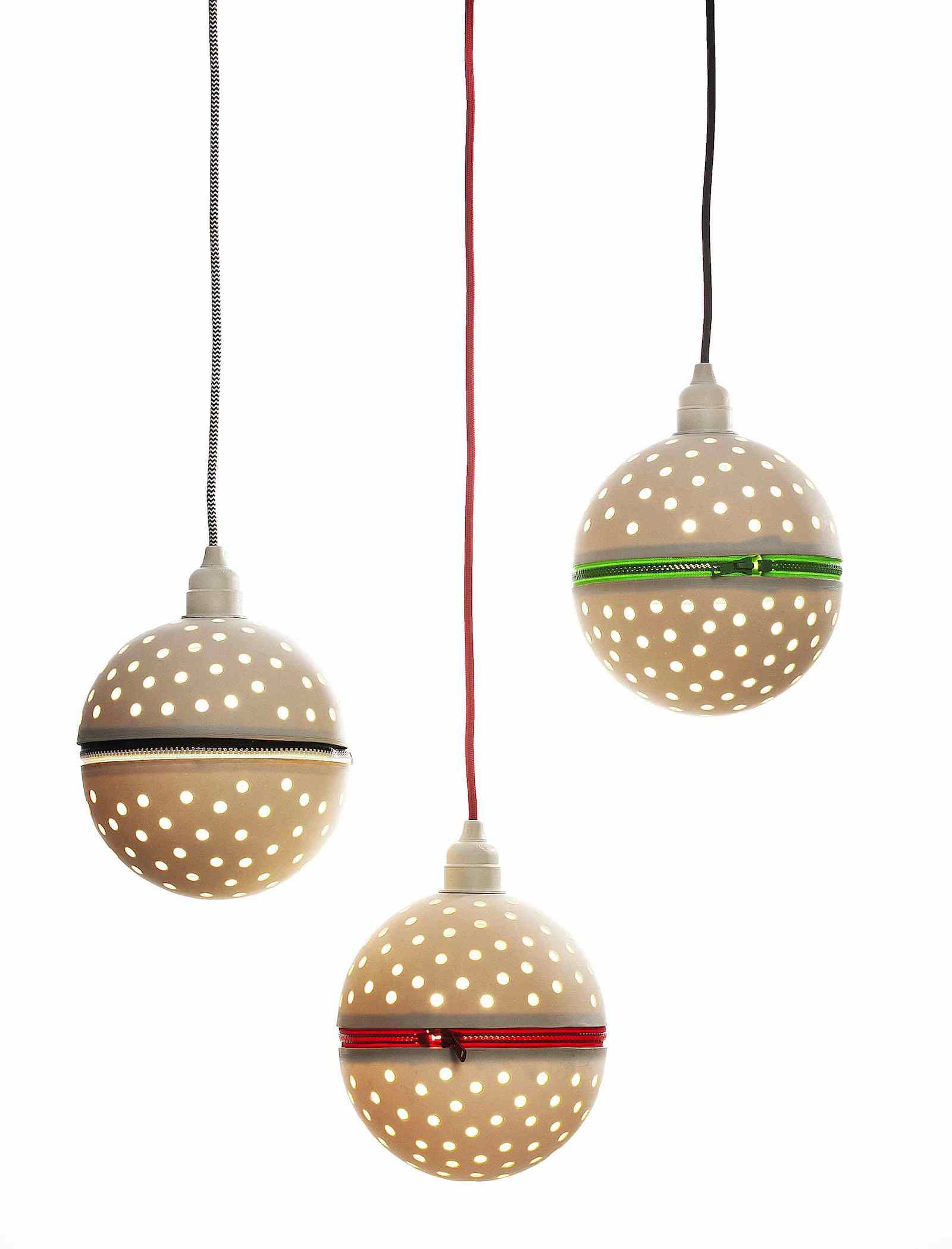 Group of three perforated porcelain globe pendants with colourful zips